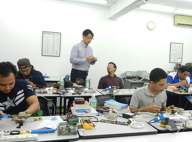 teaching students in electronics repair