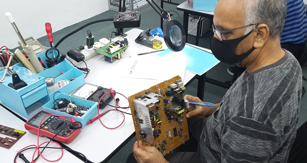 klang student taking electronics repair course
